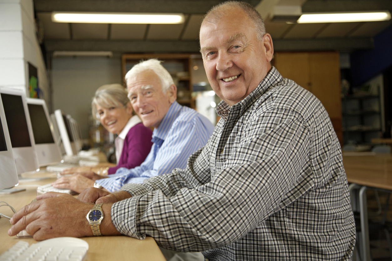 Mature woman and two mature men in computing class, portrait